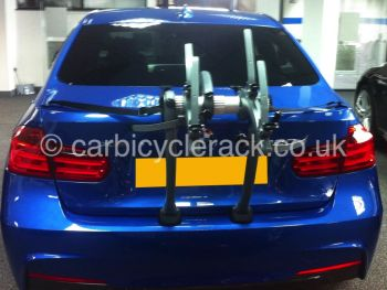 Blue BMW 3 series saloon with bike rack fitted shown from behind in BMW showroom