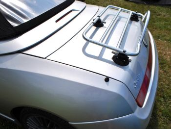 silver alfa romeo 916 spider with a luggage rack fitted to the boot in a field on a sunny day