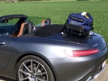 Grey AMG GTC Cabrio with a luggage rack fitted carrying a suitcase