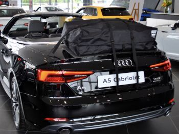 Black Audi a5 convertible with a boot-bag vacation luggage rack on the boot/trunk