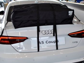 Weißes Audi A5 Coupé in einem Audi Showroom mit Gepäckablage Dachbox Dachträger montiert