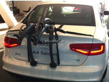 white audi a4 in a audi showroom with a two bike rack fitted