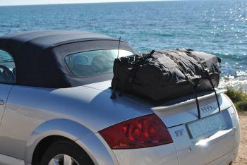 silbernes audi tt roadster cabrio mit einem gepäckträger für urlaubsgepäck am boot direkt am meer