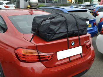 red bmw 420d outside a bmw showroom with a boot-bag roof box fitted