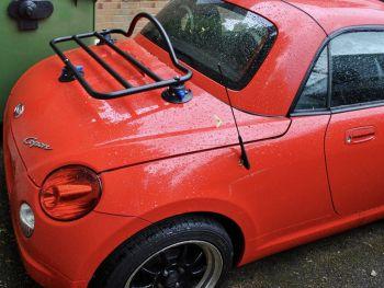rotes Daihatsu Copen Cabrio mit Gepäckträger