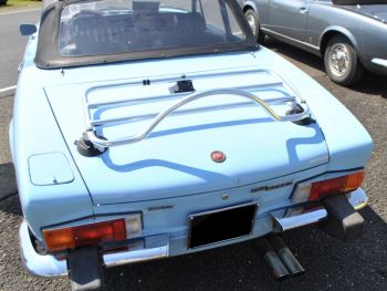 Classic light blue Fiat 124 Spider with a stainless steel luggage rack fitted on a sunny day