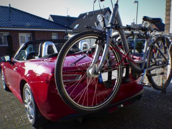 Red fiat 124 spider outside a house on sunny day with a bike rack fitted carrying a bike