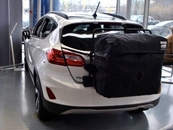 white ford fiesta with a hatchbag roof box roof rack alternative fitted to the tailgate in a ford showroom