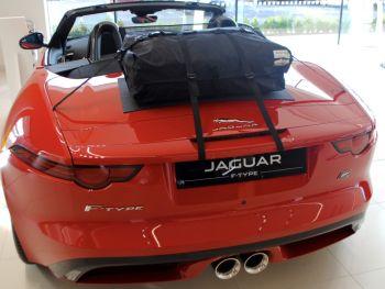 Naranja Jaguar descapotable tipo F descapotable en una sala de exposición de Jaguar con portaequipajes instalado