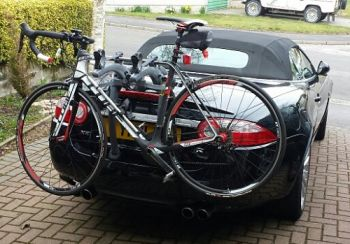 black Jaguar XK Convertible with a bike rack fitted carrying a racing bike