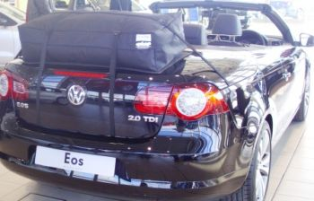 black vw eos with a boot-bag vacation luggage rack fitted in a vw showroom