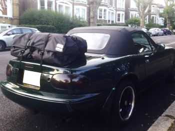 green mazda mx5 mk1 with a boot-bag vacation luggage rack fitted in a residential street