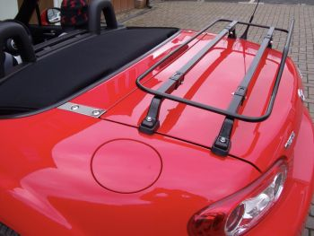 roter mazda mx5 miata nc mit einem schwarzen Gepäckträger, der dicht von der Seite außerhalb einer inländischen Garagenhaube fotografiert wurde