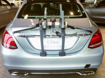 rear view of a mercedes c class saloon with a bike rack fitted in a mercedes showroom