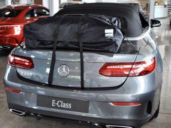 graues Mercedes-Benz E-Klasse-Cabrio mit einem Kofferraum-Urlaubsgepäckträger in einem Mercedes-Händler