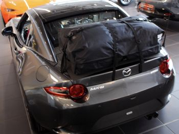 Grey miata MX5 RF with a bootbag vacation luggage rack fitted photographed from the rear