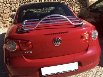 red vw eos with the roof up and a stainless steel luggage rack fitted