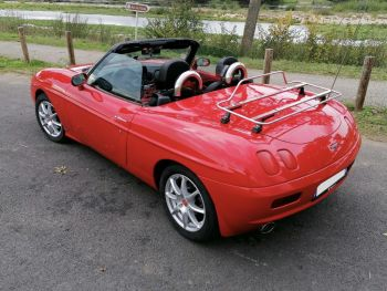 Red fiat barchetta with a stainless steel luggage rack fitted in a car park next to a stream