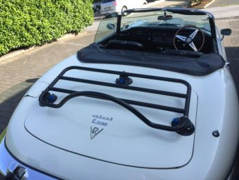 White jaguar e type convertible with a luggage rack fitted on a sunny day