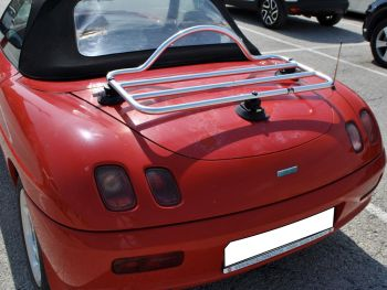 red fiat barchetta with a stainless steel / chrome luggage rack attached