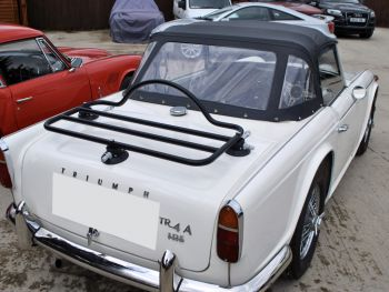 white triumph tr4 with a luggage rack fitted